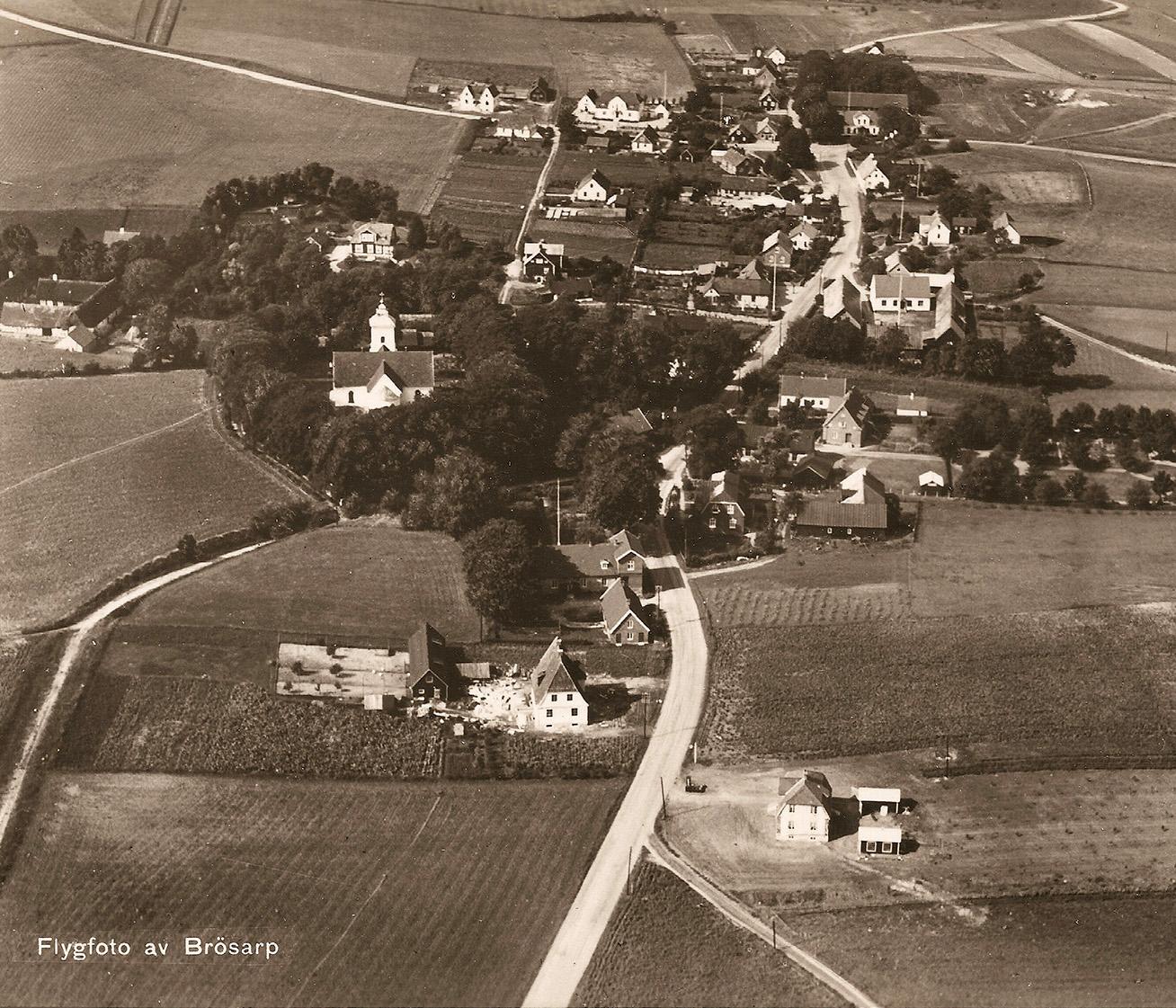 Husets historia med flygfoto över Brösarp 1935. Doktorsbostaden som nu blivit veterinärsvilla ligger halvt i skugga av träden strax under mitten av bilden. Foto: Olof Liljeqvist