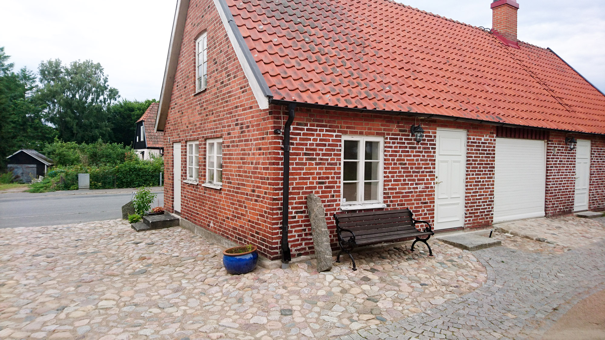 Bredvid stora huset finns ett mindre hus med billigt boende. Entrén är dörren bredvid bänken.